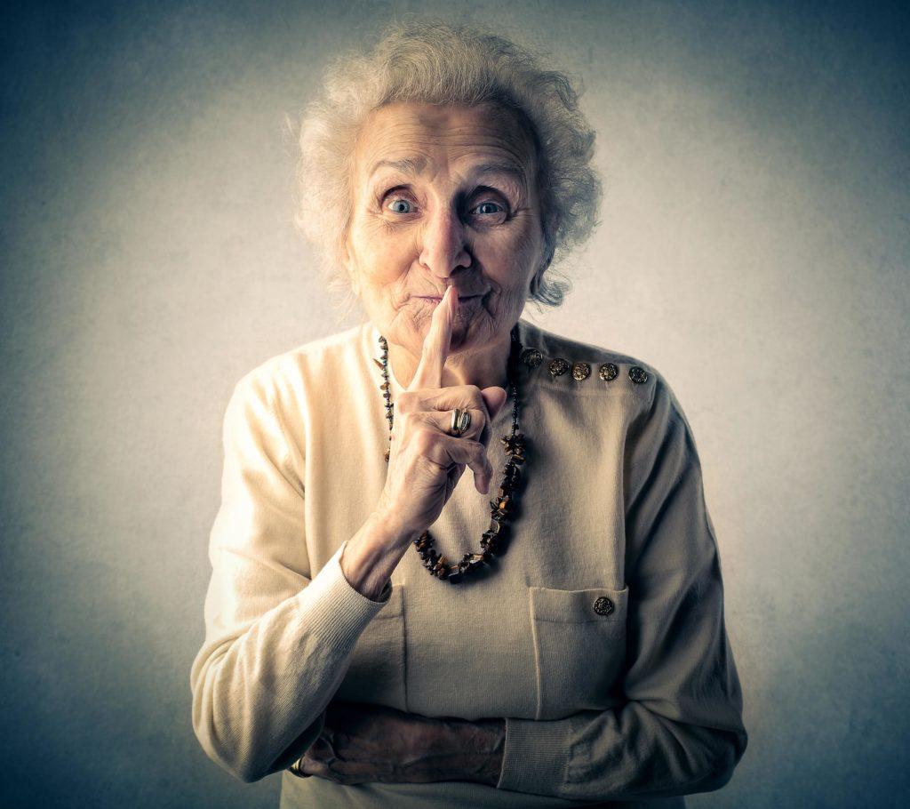 Close-up portret van oudere dame met de vinger op de lippen